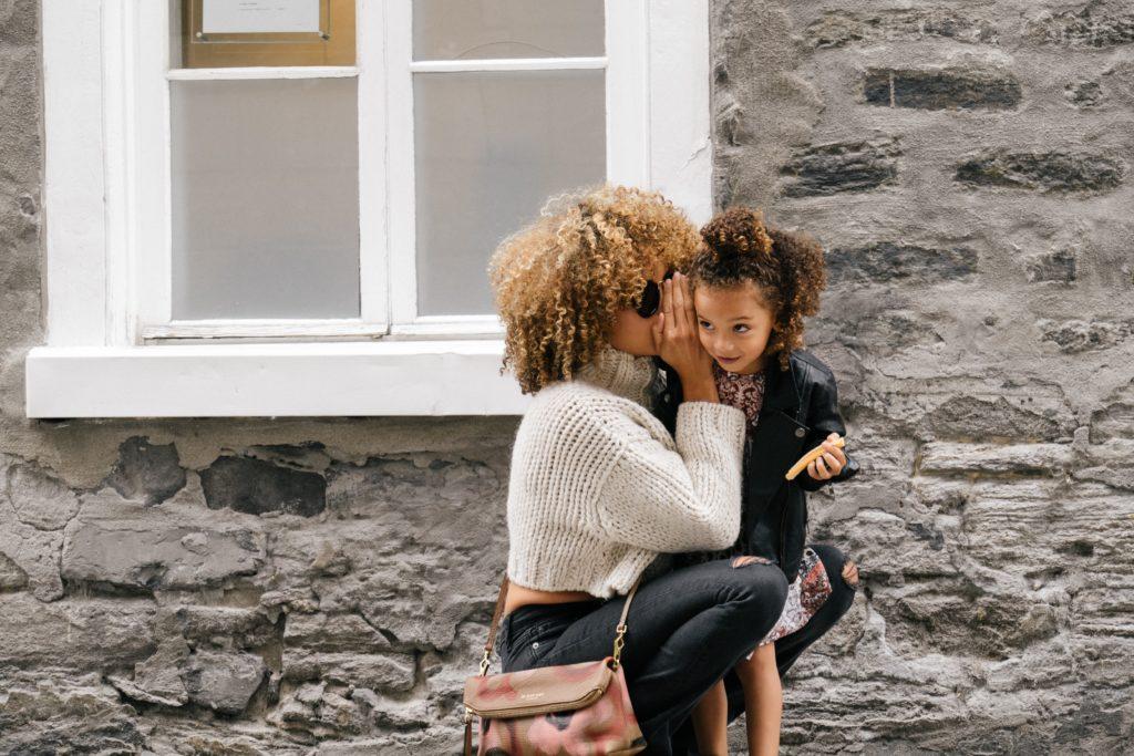 Une mère chuchote à l'oreille de sa fille.