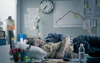 Homme endormi à son bureau avec un oreiller et un ours en peluche