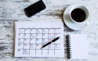 Vue en plongée sur un calendrier, un café et un smartphone